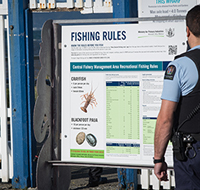 fishery officer checking fishing rules board200x190