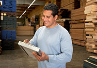 man with clipboard in a warehouse with stacked lumber